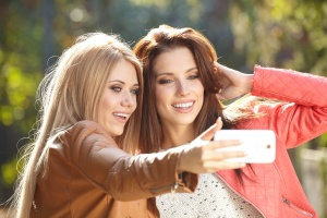 Friends making selfie. Two beautiful young women making selfie